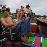 "NAPLES, FL -- March 6, 2011 -- Corrin Wagner, left, sits with ""Murdock"" and Kerry Forrest, foreground, as they watch the races during the Swamp Buggy Races at the Florida Sports Park in Naples, Fla., on Sunday, March 6, 2011.  The races originated in the 1940's by bored hunters and draws thousands of fans three times a year to take in the buggies and jeep compete in the swamp. (Chip Litherland for ESPN the Magazine)"