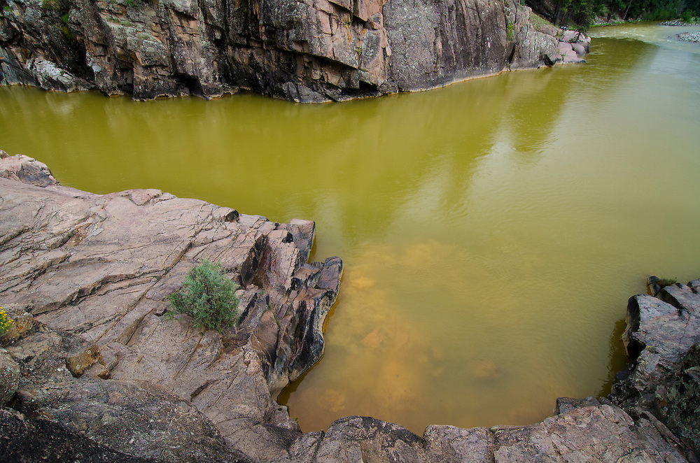 The river water, now turned a mustard yellow, sits in stark contrast to the granite shores, replacing the once aqua blue waters common to this section of the river near Baker's Bridge. A dislodged stone briefly churns up sediment from the Gold Kinf Mine spill at the river's edge.