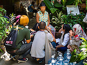 15 SEPTEMBER 2016 - BANGKOK, THAILAND: Students interview a resident of the Pom Mahakan slum about life in the old fort. Forty-three families still live in the Pom Mahakan Fort community. The city of Bangkok has given them provisional permission to stay, but city officials say the permission could be rescinded and the city go ahead with the evictions. The residents of the historic fort have barricaded most of the gates into the fort and are joined every day by community activists from around Bangkok who support their efforts to stay.                     PHOTO BY JACK KURTZ