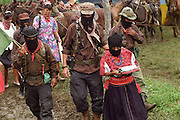 Zapatista sub commander Marcos leads Zapatista commander Ramona, to a waiting vehicle for her journey to Mexico City, 1996. To the right of Marcos is major Moises, and to the left comander Tacho.