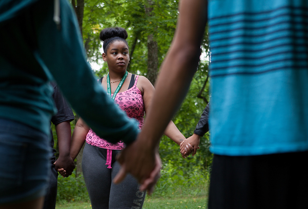 Lanita Horne and other participants in Ohio University's Junior Executive Business Program hold hands for a team exercise during the Ropes Challenge Course on July 13, 2014. Photo by Lauren Pond