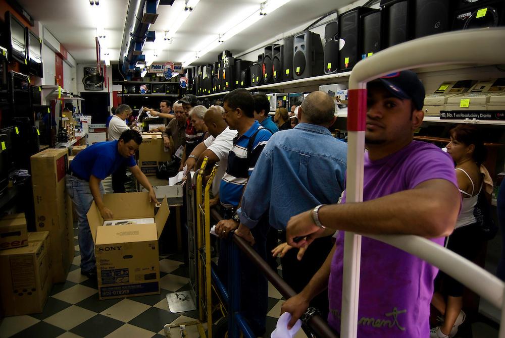 Cientos de Caraque&ntilde;os asistieron a tiendas de electrodomesticos para comprar a dolar viejo debido al aumento del dolar preferencial. Caracas, Venezuela 12-01-2010. <br /> Photography by Aaron Sosa