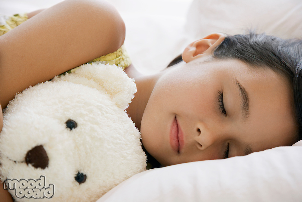Girl sleeping on bed with teddy bear head and shoulders