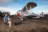 Grumman F3F vintage airplane parked in the grass with owner/restorer. (Model and Property Released)