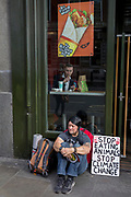 A food science protester sits outside a McDonalds restaurant in Whitehall during the environmental protest about Climate Change occupation of Trafalgar Square in central London, the third day of a two-week prolonged worldwide protest by members of Extinction Rebellion, on 9th October 2019, in London, England.