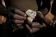 A worker is holding a piece of ore containing gold, in an artisanal processing site near Abare, a village affected by lead poisoning due to the unsafe techniques employed for extracting gold, in Zamfara State, Nigeria. The contamination is caused by ingestion and breathing of particles released in the steps to isolate the gold from other metals. This type of lead is soluble in stomach acid and children under-5 are most affected, as they tend to ingest more through their hands by touching the ground, and are developing symptoms often leading to death or serious disabilities.