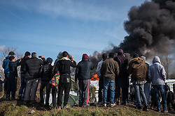 Licensed to London News Pictures. Calais, France. 03/03/16.  Refugees watch and film on their mobile phones as a shelter burns with thick black smoke. French authorities are clearing the southern half of the Calais 'Jungle' camp, which charities estimate to contain 3,500 people.. Photo credit : Rob Pinney/LNP