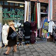 Nederland Den Haag 26 november 2008 2081126 Foto: David Rozing..Vrouw bekijkt naar uitgestalde kleding bij een winkel speciaal voor islamitische spullen in achterstandswijk Schilderwijk .De schilderwijk is een van de 40 wijken van Vogelaar. Deze lijst van 40 Nederlandse probleemwijken is op 22 maart 2007 door Minister Ella Vogelaar van Wonen, Wijken en Integratie bekend gemaakt. De minister duidde deze wijken aan met prachtwijken. In deze wijken zullen gedurende de kabinetsperiode Balkenende IV extra investeringen worden gedaan gezien stapeling van sociale, fysieke en economische problemen die zich daar voordoen..De wijk is in de tweede helft van de 19e eeuw gebouwd. Het is een van de armste wijken in Nederland. Zo'n 87% van de 33.123 geregistreerde bewoners is van niet Westerse afkomst  met name Turks, Surinaams en Marokkaans..De Schilderswijk is rijk aan verschillende culturen die boven en naast elkaar leven. .Foto: David Rozing