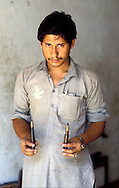 Pakistan   1986..A Pakistani tribal man with a bullet  that is manufactured..Darra Adamkhel is Pakistan's largest weapons bazaar and factory, renowned for its gun making expertise since the late 19th century, Darra is a sprawl of hundreds of workshops where some 3,500 gunsmiths toil on replica weapons.
