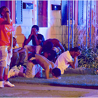 Bystanders react at the scene of a multiple shooting near the intersection of West 29th and Summit streets in the early morning hours of Saturday, July 25, 2015 in Erie, Pa. Six were shot in the incident, which was reported just before midnight on July 24. One additional person was wounded in a crash involving shooting suspects not far from the scene. The fatal shooting ended up claiming the lives of two victims, both 16-year-old Erie residents. One teen, Elijah Jackson, was pronounced dead at the scene while a second, Shakur Franklin, died at from his injuries at the nearby UPMC Hamot hospital on July 25. In the days following, family and friends gathered at the site to remember the teens in vigils and at makeshift memorials near where they were shot. The Erie County Coroner's Office determined that both teens' deaths were homicides, prompting a deeper investigation by Erie police.