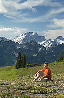 Hiker contemplating the view from Miner's Ridge. Dome Peak in the distance, Glacier Peak Wilderness North Cascades Washington