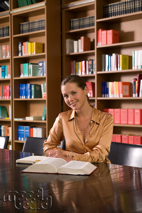 Young woman with book at desk in library portrait