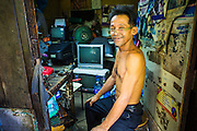 """11 JANUARY 2013 - BANGKOK, THAILAND:    A repair shop owner in his shop in the Ban Krua neighborhood in Bangkok. The Ban Krua neighborhood of Bangkok is the oldest Muslim community in Bangkok. Ban Krua was originally settled by Cham Muslims from Cambodia and Vietnam who fought on the side of the Thai King Rama I. They were given a royal grant of land east of what was then the Thai capitol at the end of the 18th century in return for their military service. The Cham Muslims were originally weavers and what is known as """"Thai Silk"""" was developed by the people in Ban Krua. Several families in the neighborhood still weave in their homes.               PHOTO BY JACK KURTZ"""