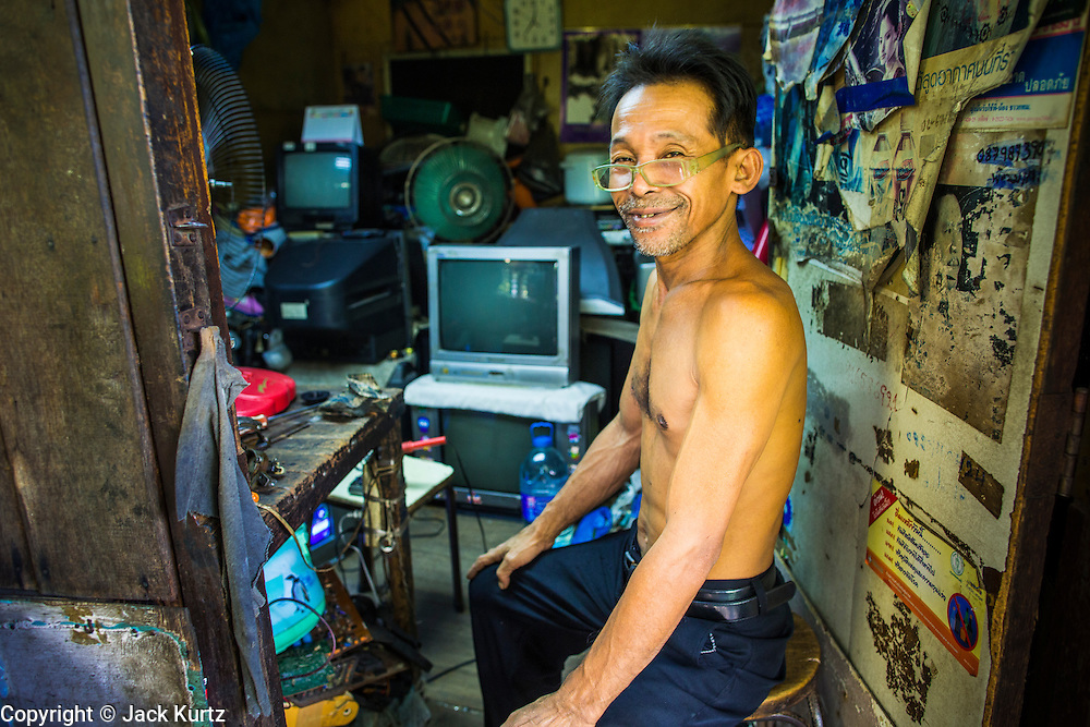 "11 JANUARY 2013 - BANGKOK, THAILAND:    A repair shop owner in his shop in the Ban Krua neighborhood in Bangkok. The Ban Krua neighborhood of Bangkok is the oldest Muslim community in Bangkok. Ban Krua was originally settled by Cham Muslims from Cambodia and Vietnam who fought on the side of the Thai King Rama I. They were given a royal grant of land east of what was then the Thai capitol at the end of the 18th century in return for their military service. The Cham Muslims were originally weavers and what is known as ""Thai Silk"" was developed by the people in Ban Krua. Several families in the neighborhood still weave in their homes.               PHOTO BY JACK KURTZ"