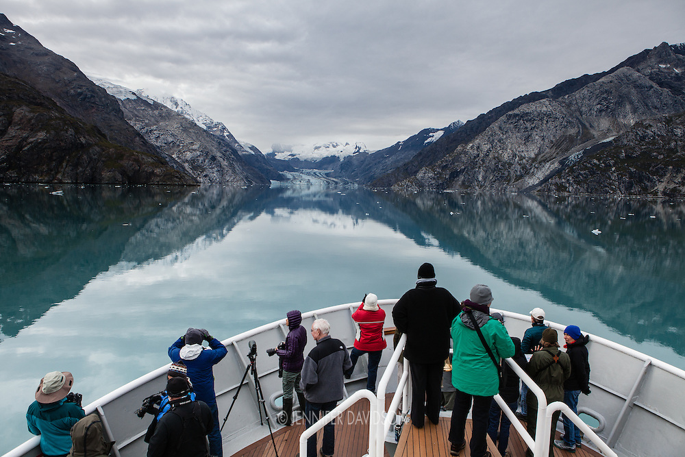 Guests onbaord the National Geographic Sea Lion look out over Johns Hopkins Glacier from the ship's bow in Glacier Bay National Park, Alaska.