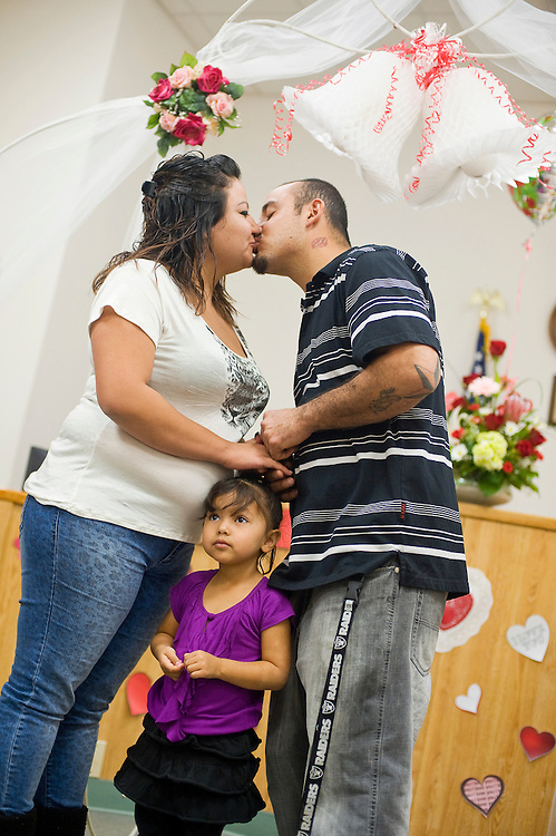 021413       Brian Leddy<br /> Donovan Alonzo and Alicia Olguin kiss after being married while standing with their daughter Sierra Olguin Thursday at Magistrate Court. The couple was one of about 10 people that chose to get married on Valentine's Day.