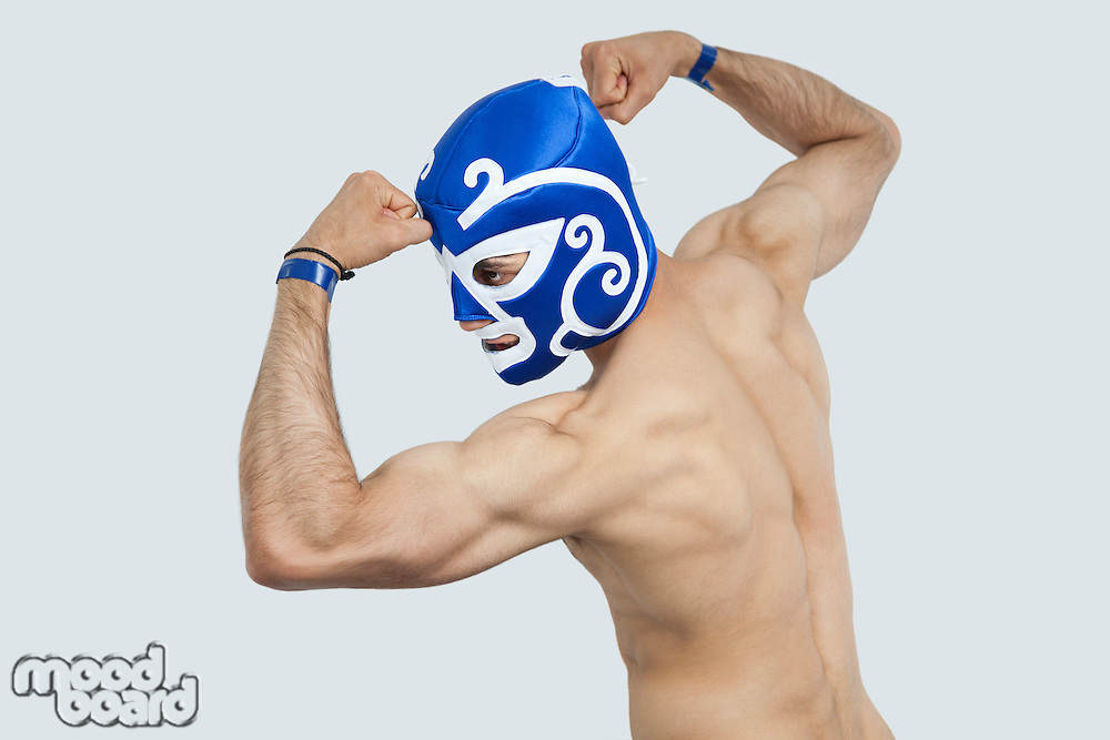 Rear view of a shirtless man in wrestling mask flexing muscles over gray background