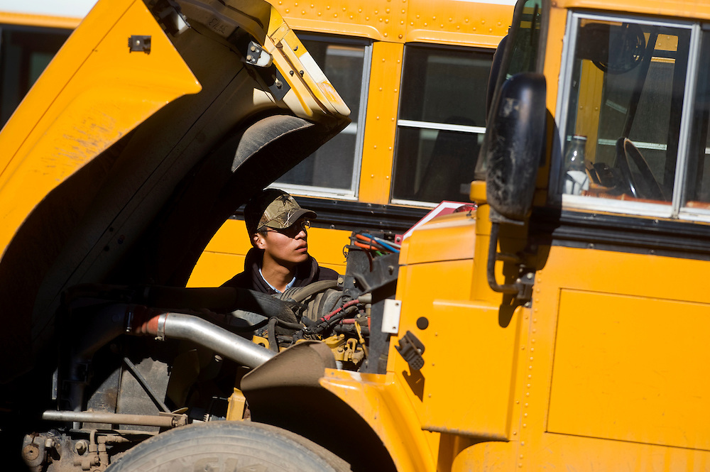 021111       Brian Leddy.Valentino Haley does an engine check before starting his bus on Friday at the Gallup-McKinley County Schools bus barn.
