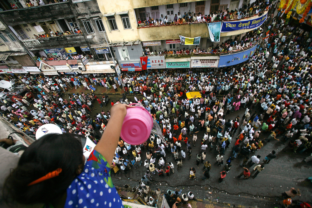 "A woman pours water on devotees attempting to break a pot containing butter on the occasion of Krishna Janmashtami (birth of lord Krishna) in Mumbai, September 4, 2007. Janmashtami, which marks the birthday of Hindu god Krishna, will be celebrated across the country on September 4. As legend goes Lord Krishna as a child ate butter kept out of his reach by forming a human pyramid with his friends. Today these ""pots of butter"" contain lakhs of Indian currency as prize money. People form multistoried layers and are ready to risk serious injuries. Photographer: Prashanth Vishwanathan"