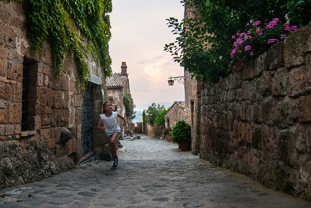 A girl runs towards the streets of the village of Civita di Bagnoregio.<br /> Civita di Bagnoregio is a town in the Province of Viterbo in central Italy, a suburb of the comune of Bagnoregio, 1 kilometre (0.6 mi) east from it. It is about 120 kilometres (75 mi) north of Rome. Civita was founded by Etruscans more than 2,500 years ago. Bagnoregio continues as a small but prosperous town, while Civita became known in Italian as La citt&agrave; che muore (&quot;The Dying Town&quot;). Civita has only recently been experiencing a tourist revival. The population today varies from about 7 people in winter to more than 100 in summer.The town was placed on the World Monuments Fund's 2006 Watch List of the 100 Most Endangered Sites, because of threats it faces from erosion and unregulated tourism.