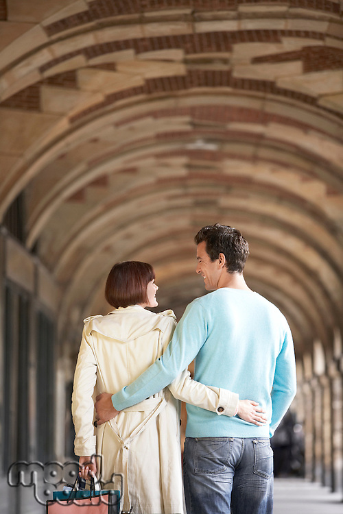 Couple with arms round each other walking through archway back view