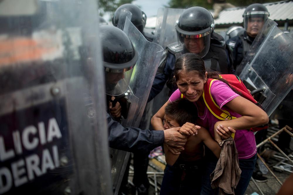 Madre e hijo huyen aterrorizados después de que la Policía Federal mexicana lanzara gases lacrimógenos para bloquear el acceso de los migrantes a suelo mexicano, en el puente fronterizo entre Guatemala y México. Tecún Umán, Guatemala. 19/10/2018 <br /> <br /> A mediados de octubre 2018, miles de migrantes hondureños abandonaron sus casas para emprender el viaje hasta los Estados Unidos, recorriendo casi 5.000 kilómetros hasta la ciudad fronteriza de Tijuana en menos de dos meses.<br /> Las 10.000 personas (según estimaciones de la UNCHR) que conformaron la caravana visibilizaron el fenómeno migratorio por primera vez en Centroamérica, denunciando las problemáticas de extrema pobreza y violencia presentes en los lugares de origen.