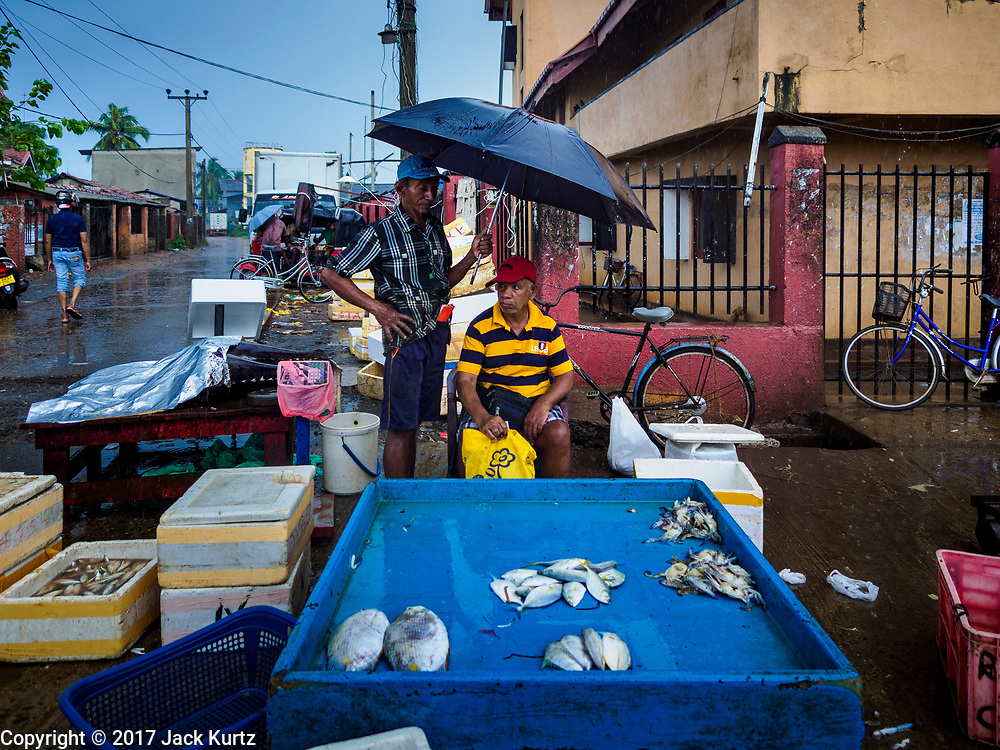 08 OCTOBER 2017 - NEGOMBO, WESTERN PROVINCE, SRI LANKA: A fish monger selling fish in the rain in Negombo, north of Colombo. Fish is an important source of protein for many Sri Lankans.    PHOTO BY JACK KURTZ