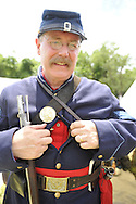 Old Bethpage, New York, USA - July 21, 2012: MIKE SCALLION of Dix Hills, NY, unbuttons military jacket to show red wool shirt soldiers wore in summer, as he portrays a Private, at re-creation of Camp Scott, a Union Army training camp, at Old Bethpage Village Restoration, to commemorate 150th Anniversary of American Civil War, on Saturday, July 21, 2012.