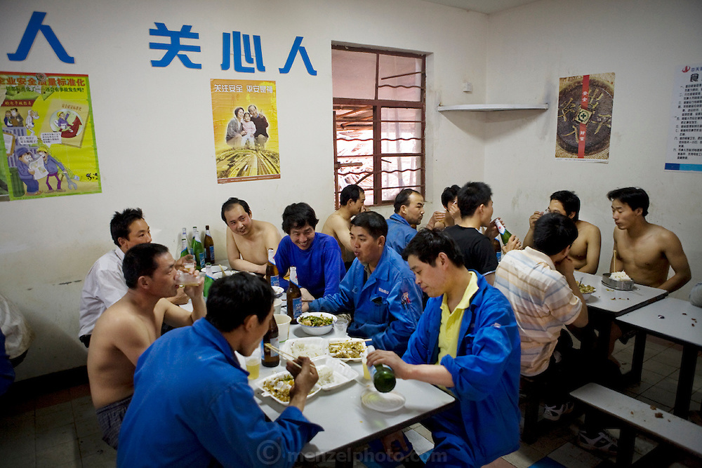 Workers enjoy a meal in the cafeteria of a construction company building the Zhrong Rong Jasper Tower in Pudong, Shanghai, China. (From the book What I Eat: Around the World in 80 Diets.)  In China, migrant laborers often live directly on the job-site grounds of big construction projects and work 12-hour shifts, seven days a week. Alcohol is only tolerated in the company cafeteria after dinner.