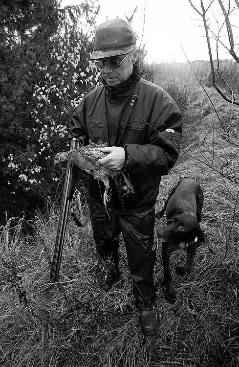 The hunter exames a partridge he shoot and his dog fetched a the hunting place in the countryside of the Danish island Funen on sunday  17. November 2002.  Photo: Erik Luntang