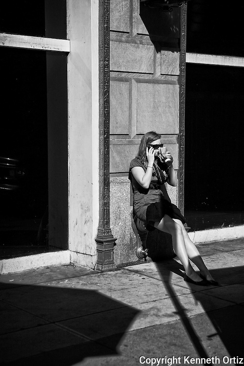 A young woman taking a break and sipping her coffee while talking on her cell phone, near 55th Street and 5th Avenue.