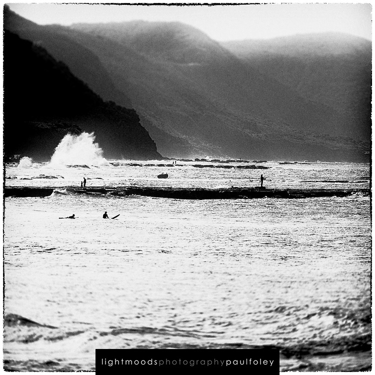 Moody black and white view of afternoon coastline activities at Coledale Beach, NSW, Australia