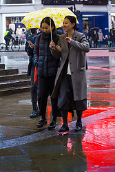 Two women share an umbrella as the lights from the famous illuminated signs of Piccadilly Circus are reflected in the pavement. As forecasters predicted, the rain arrives in London where Londoners and tourists go about their business. London, February 13 2018.