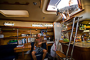 Surfer Ernie Johnson at home in his 38 foot sailboat moored at Dana Point Harbor in California. (Ernie Johnson is featured in the book What I Eat: Around the World in 80 Diets.) MODEL RELEASED.