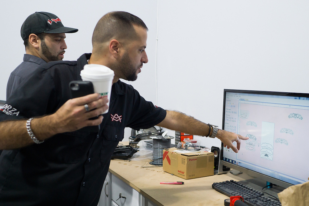 DORAL, FLORIDA, DECEMBER 11, 2015<br /> Arael Velazquez, left, and Alex Vega look at designs on a monitor in The Auto Firm, a South Florida car customizing and restoring shop owned by Vega which has a vast clientele of professional athletes and entertainers.<br /> (Photo by Angel Valentin/Freelance)