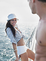 Young woman and man flirting on yacht