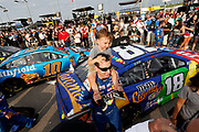 Kyle Busch carries his three-year-old son Brexton, before the start of a NASCAR Cup Series auto race at Kansas Speedway in Kansas City, Kan., Saturday, May 12, 2018. (AP Photo/Colin E. Braley)