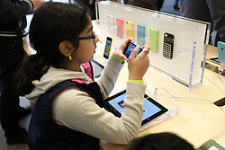 © Licensed to London News Pictures. 27/10/2013. London, UK.  A child plays with an Apple iPhone 5C on display at Apple's UK flagship store in Regent Street, today 27 October.  Apple is to announce its Q4 Fiscal Results tomorrow - the company launched the iPhone 5C in the closing weeks weeks of the quarter to as a lower cost option in an effort to attract budget users  . Photo credit : Richard Isaac/LNP