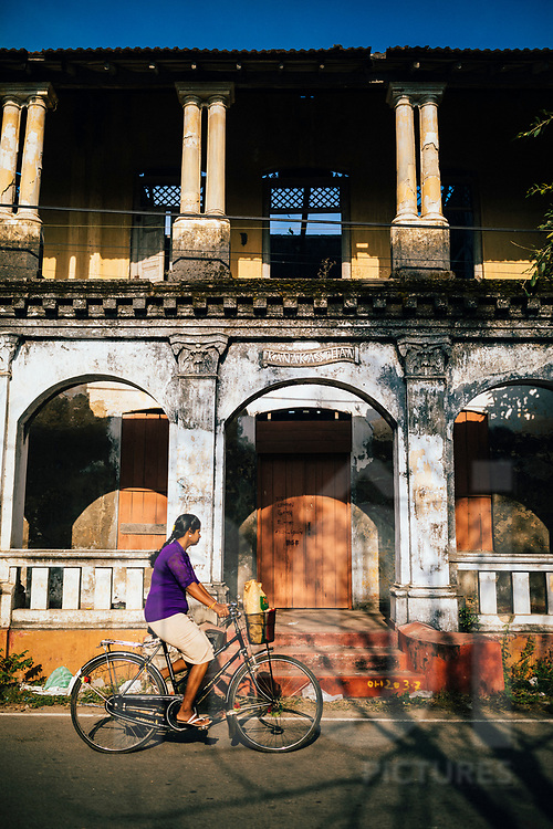 A woman rides her bicycle past an old building, Jaffna, Sri Lanka, Asia