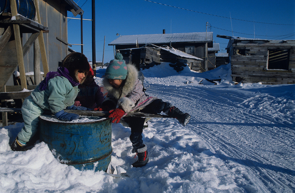 USA, Alaska, Eskimo children play on old oil drum in western Alaska village of Kotlik