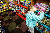"Macey Blackwell, 5, browses the ""My Little Pony"" book section Tuesday at Hastings Books in Coeur d'Alene as she shops for books to purchase for other children in the community. A number of children took part in an event designed to teach them the true meaning of holiday giving. All of the purchased books will be donated to Books For Tots."