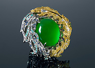 white and yellow gold surround a large oval green Jade stone designed by Anna Hu