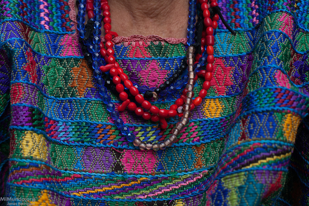 Detail of the beads worn by Antonia Osorio Sanchez, 62, survivor from Rio Negro. She hopes the Forensic Anthropology Foundation of Guatemala (FAFG) identifies and returns her sister-in-law Maria Tahuico Morales, thirty-five years old at the time of her killing or abduction during the May 14, 1982, Los Encuentros Massacre and possibly exhumed in 2012 from grave XV at the UN's CREOMPAZ training center, formerly Coban's Military Zone 21. During the massacre, Guatemalan soldiers and civil patrolmen killed 79 community members from Rio Negro who were hiding here after the previous two massacres of February and March of the same year. Eyewitnesses assured that at least 15 other community members were abducted in a helicopter. As of May 2016, CREOMPAZ's grave XV has rendered positive DNA matches of the remains of two victims abducted in the helicopter on such day. Antonia, who is the closest living relative to Maria Tahuico Morales, is not sure if she was killed in Los Encuentros or taken by Helicopter. Antonia lives in Pacux, the resettlement village outside Rabinal where the former Achi Mayan residents of Rio Negro were forcibly relocated after the massacres and destruction of their village and dozens more due to the flooding of the Chixoy river basin and construction of the Chixoy Hydro-electric project. Pacux, Rabinal, Baja Verapaz, Guatemala. May 20, 2016.