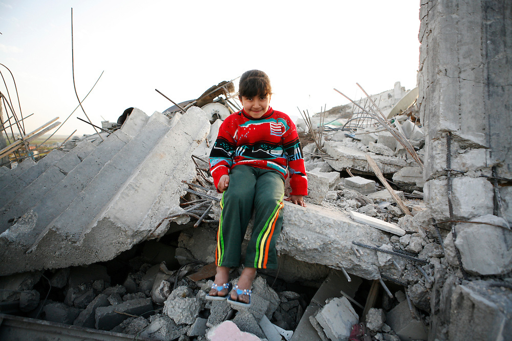 Palestinian children sit atop their home destroyed by Israel in Jabaliya in the Gaza Strip.