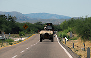 A heavily armed military convoy patrols the highway in Sonora, Mexico between Nogales and Magdalena.  The area has seen an increase in violence between cartel rivals.