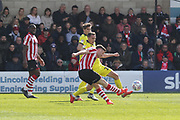 Shay McCartan scores the opening goal under pressure from Jordan Tilson  during the EFL Sky Bet League 2 match between Lincoln City and Cheltenham Town at Sincil Bank, Lincoln, United Kingdom on 13 April 2019.