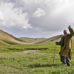 Old Kyrgyz shepherd walking near his yurt. Song Kol lake. Kyrgyzstan.