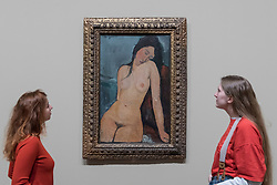 "© Licensed to London News Pictures. 21/11/2017. London, UK.  Staff members view ""Female Nude"", 1916. Preview of ""Modigliani"", the most comprehensive exhibition of works by Amedeo Modigliani ever held in the UK.  On display are iconic portraits, sculptures and 12 nudes, the largest group ever shown in the UK.  The show runs 23 November to 2 April 2018.  Photo credit: Stephen Chung/LNP"