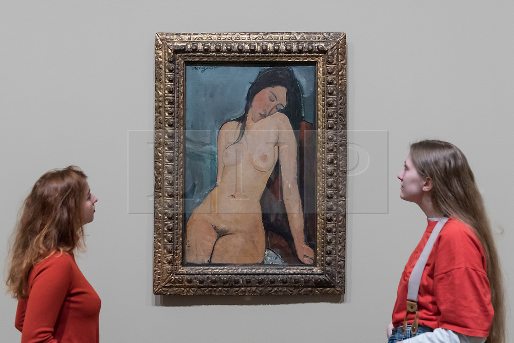 """© Licensed to London News Pictures. 21/11/2017. London, UK.  Staff members view """"Female Nude"""", 1916. Preview of """"Modigliani"""", the most comprehensive exhibition of works by Amedeo Modigliani ever held in the UK.  On display are iconic portraits, sculptures and 12 nudes, the largest group ever shown in the UK.  The show runs 23 November to 2 April 2018.  Photo credit: Stephen Chung/LNP"""