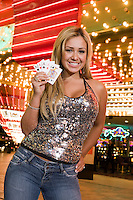 Portrait of young woman holding playing cards in front of illuminated casino, Las Vegas, Nevada, USA